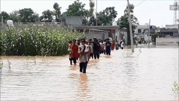 Residents forced to walk through water as flood ravages village