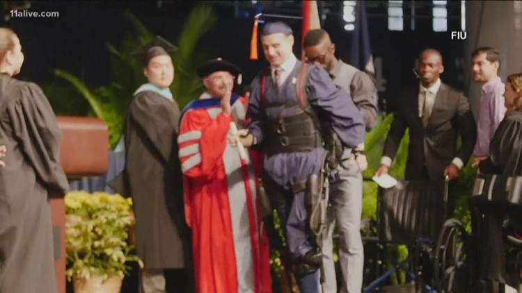 Man in wheelchair walks across stage at graduation