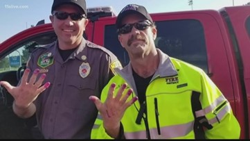 Firefighters calm girl at crash scene with nail painting