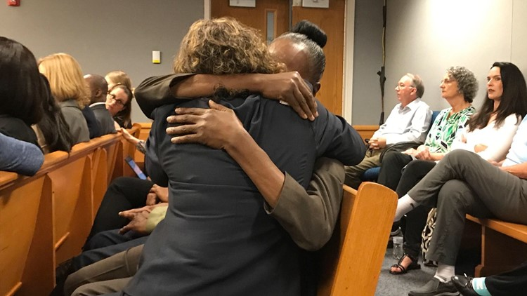 Emani Moss' teacher and grandmother hug after she testifies about having her in the 4th grade.