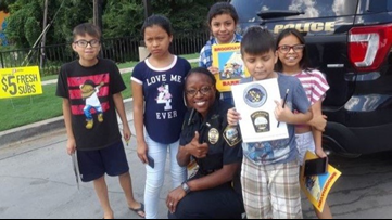 Friendly officer uses coloring books to teach street smarts