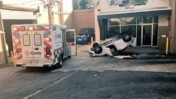 Man's car goes through parking lot fence, flips onto business' roof before hitting the ground