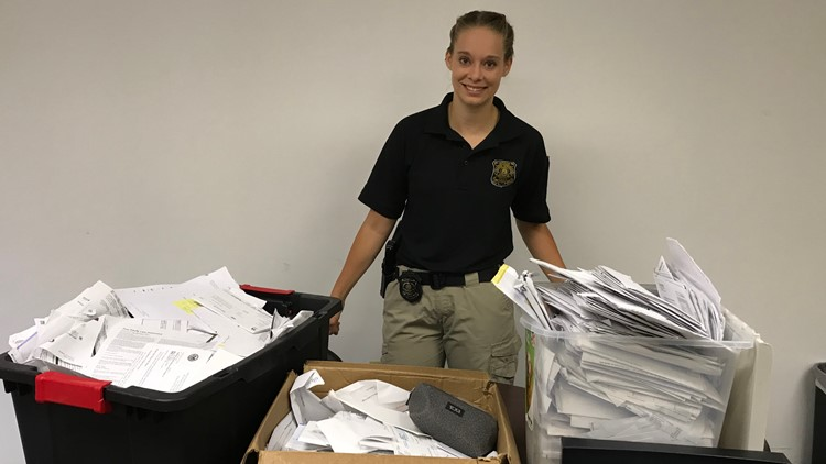 Detective standing with hundreds of pieces of mail collected as evidence