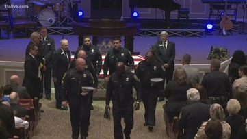 Congregation stands as law enforcement leaves Officer Michael Smith's funeral