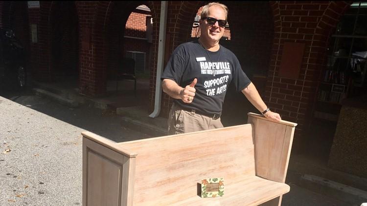 Pastor Atkins standing next to refurbished pew