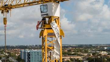 Man with banner scales crane before Trump speech in Florida