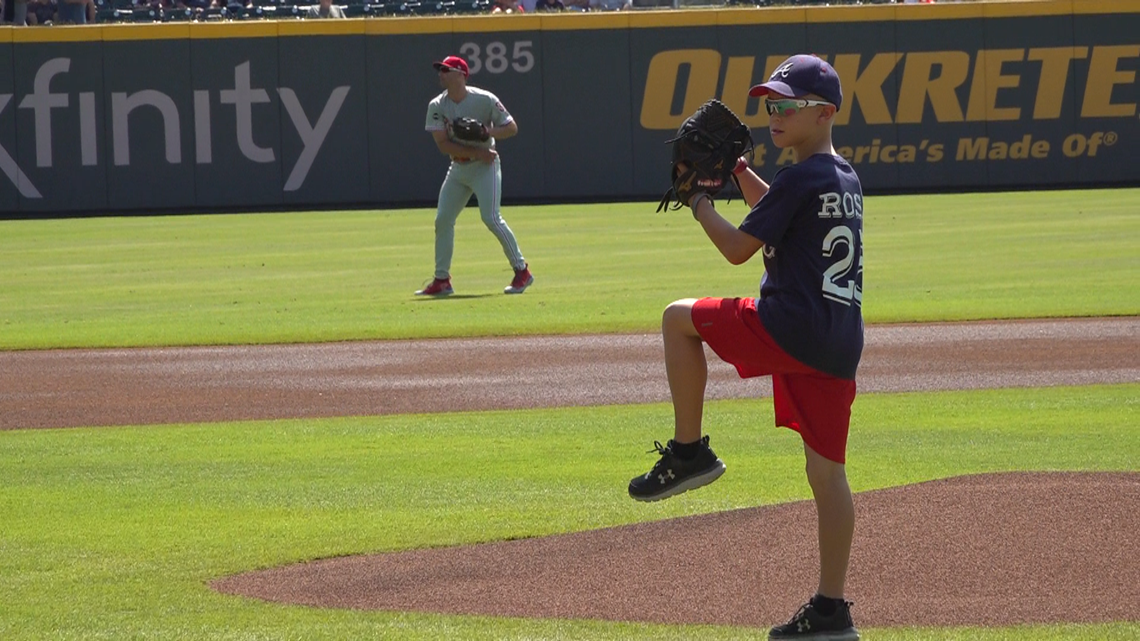 8-year-old cancer survivor throws first pitch at Braves game
